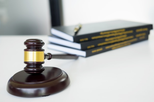 Gavel judge hammer with legal book on brown wooden desk with copy space. legislation concept.