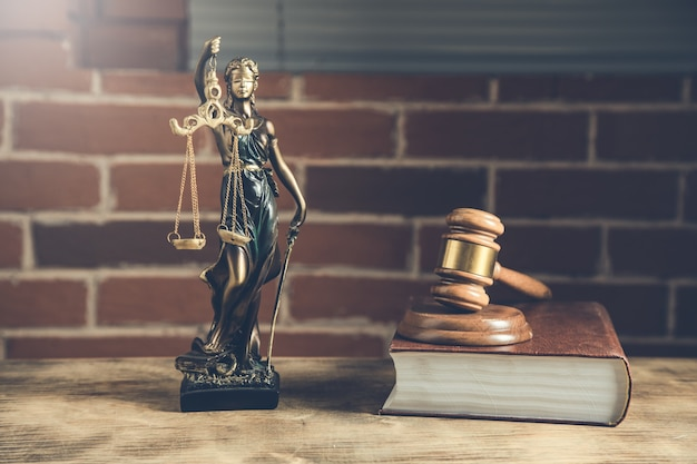 Молоток судьи по книге и дама правосудия на столе
