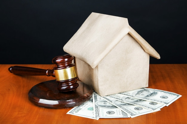 Gavel,model of house and money on table on black surface