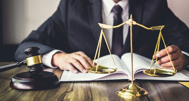 Молоток на деревянном столе и советник или юрист, работающий над документами в юридической фирме