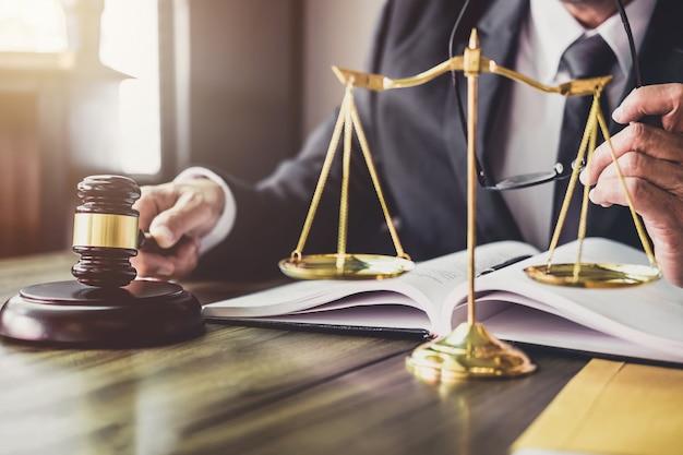 Молоток на деревянном столе и советник или юрист, работающий над документами. правовое право