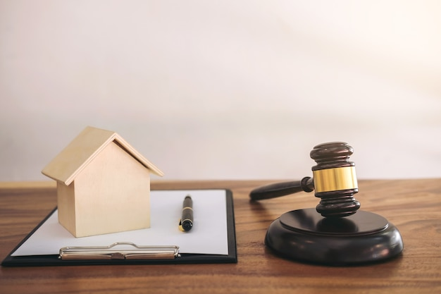 Gavel on sounding block at courtroom for decide home insurance, law and justice concept