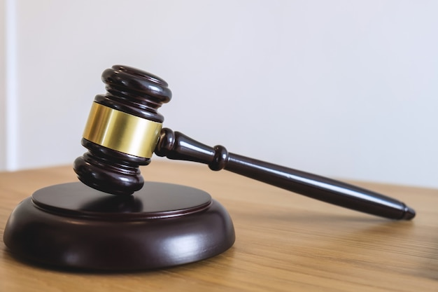 Gavel on sounding block, object and law book to working with judge agreement in courtroom