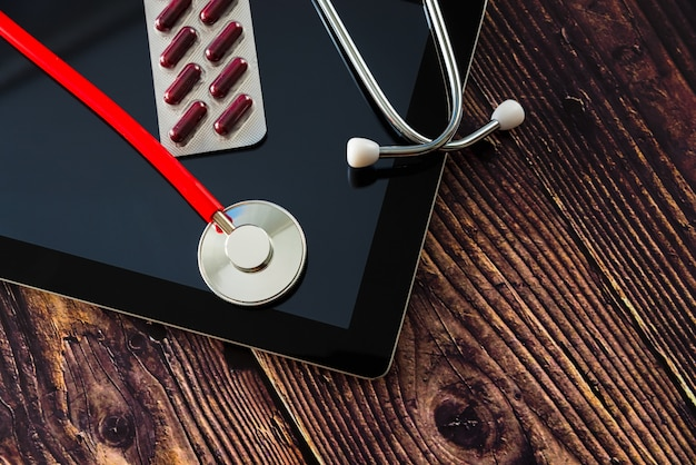 Gavel and stethoscope on wooden background, dark environment.