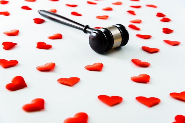 Gavel surrounded by red hearts isolated on white