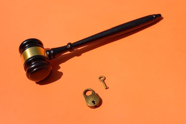 Молоток с замком, изолированные на оранжевом фоне.