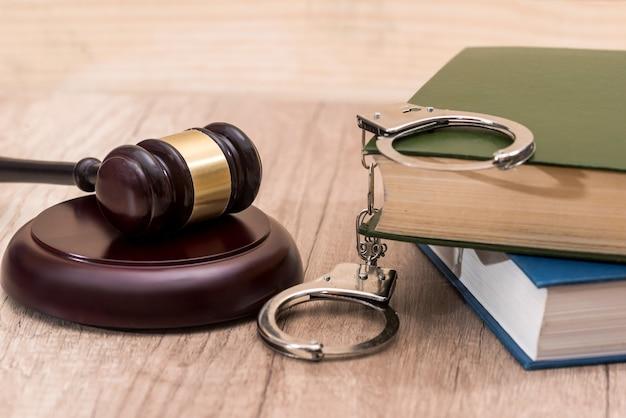 机の上に本と手錠をかけたガベル