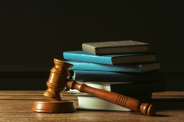 Gavel with books on old wooden desk