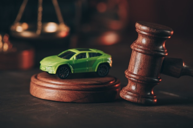 Gavel with a car model on a wooden table