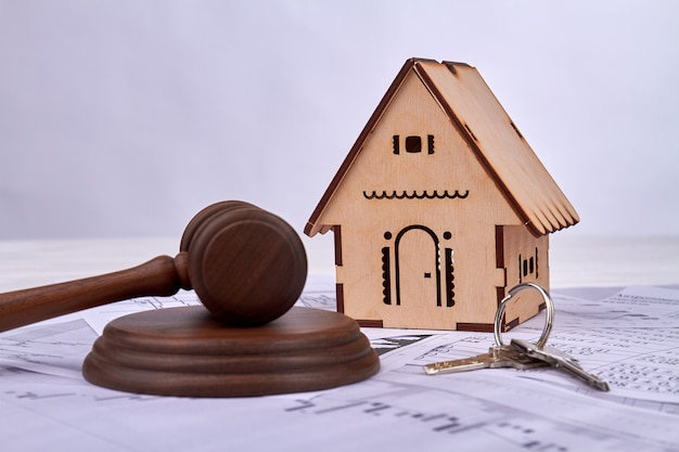 Gavel with house model and keys.