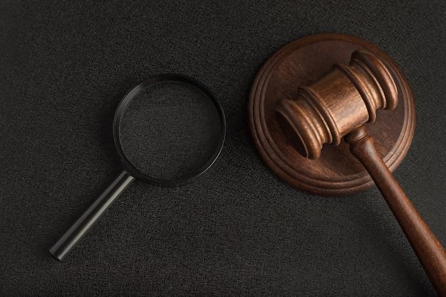 Молоток с увеличительным стеклом на черном фоне. судебно-медицинское расследование. сбор доказательств. понятие юриспруденции.