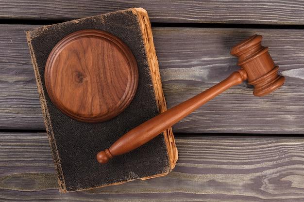 響きのブロックと古い法律の本が付いているガベル。上面図フラットレイ。判断と罰の概念。