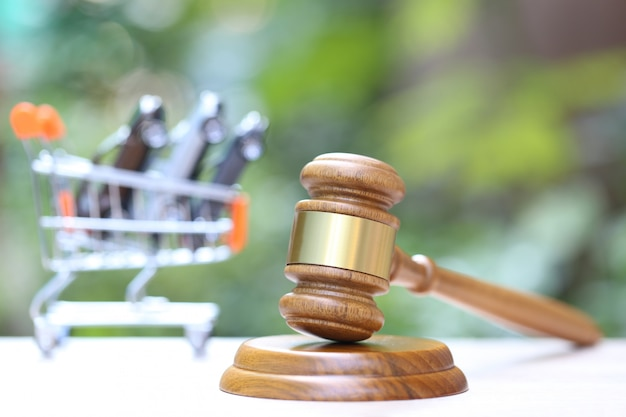 Gavel wooden and miniature car model in shopping cart