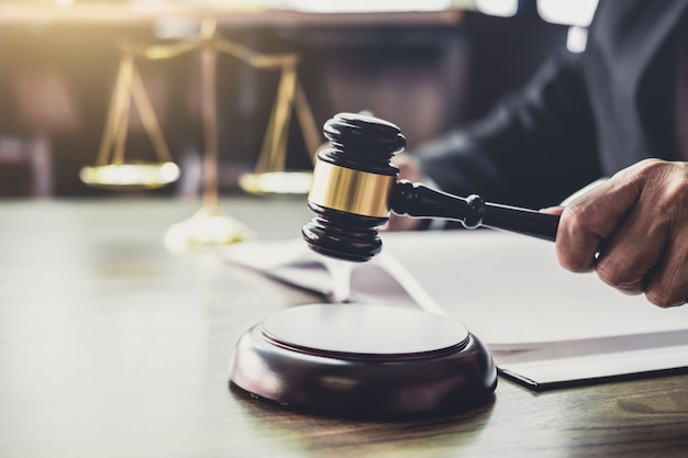 Gavel on wooden table and counselor or male lawyer working on a documents. legal law