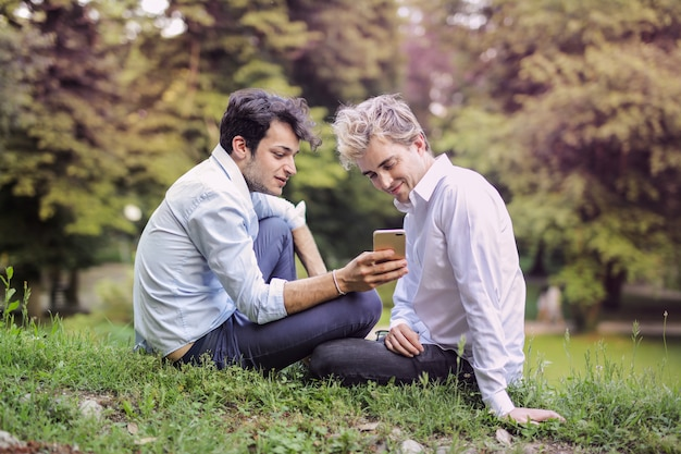 Gay couple checking a smartphone in the park