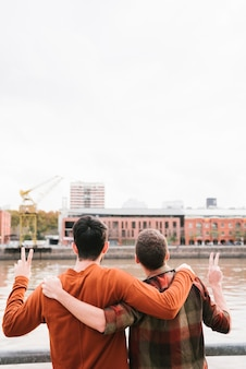Gay couple cuddling on river embankment and gesturing victory