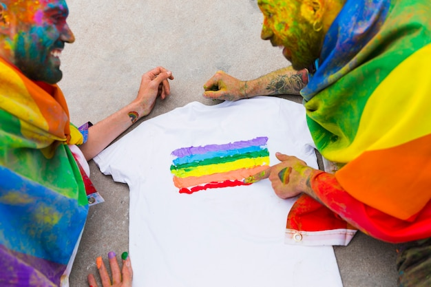 Gay couple drawing rainbow flag on t-shirt