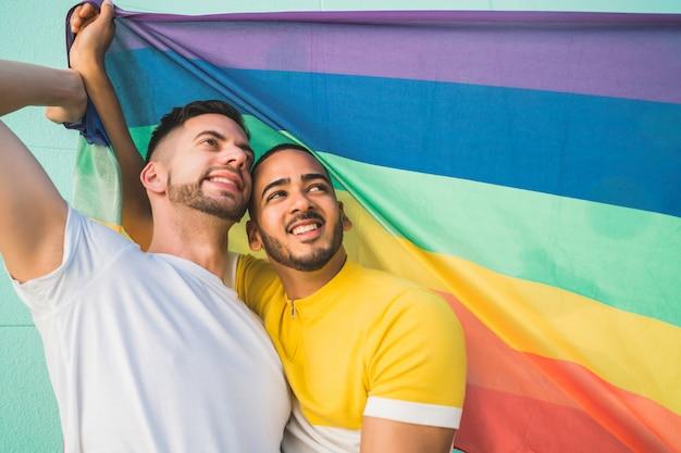 Гей пара обнимает и показывая свою любовь с радужным флагом.