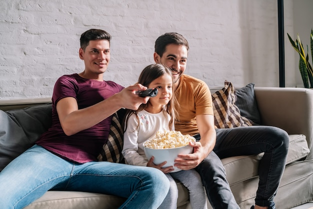 A gay couple enjoy watching movies with their daughter while sitting together on a couch at home. family concept.
