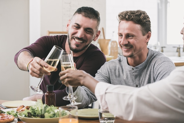 Gay couple having dinner party with friend at home