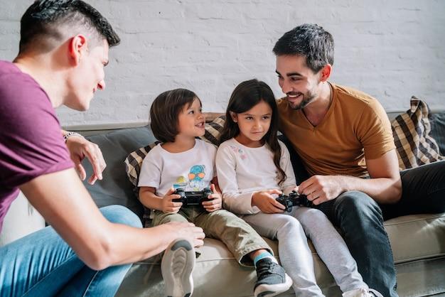 自宅で子供たちとビデオゲームをしながら楽しんでいる同性愛者のカップル。家族の概念。