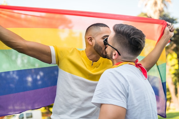 Gay couple kissing and showing their love with rainbow flag.