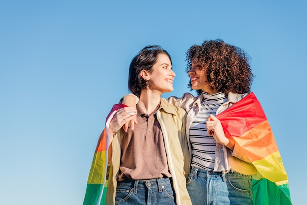 Gay couple of lovely women with a rainbow flag