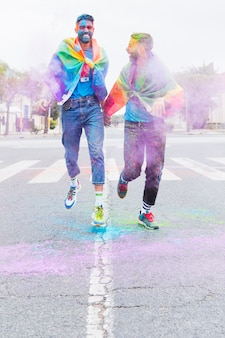 Gay couple in multicolored holi powder running down road