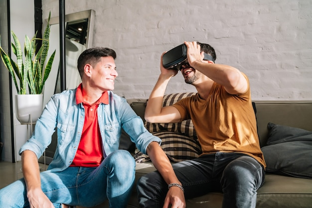 Gay couple playing video games with vr glasses while sitting together on a couch at home.