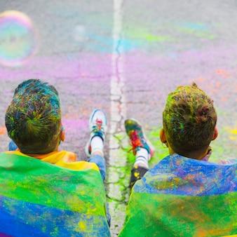 同性愛者のカップルが通りに座って虹色の旗