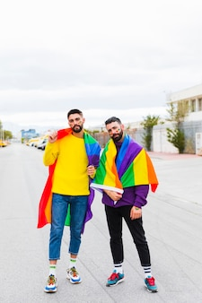 Gay couple standing with rainbow flag on road