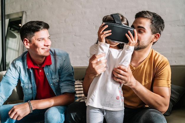 Gay couple and their kids playing video games with vr glasses together at home. family concept.