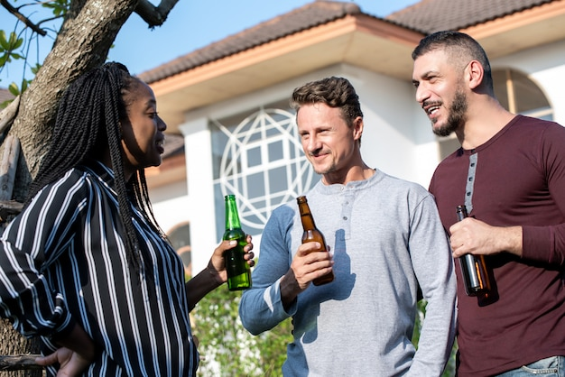 Gay couple and woman friend enjoying chatting and drinking alcohol