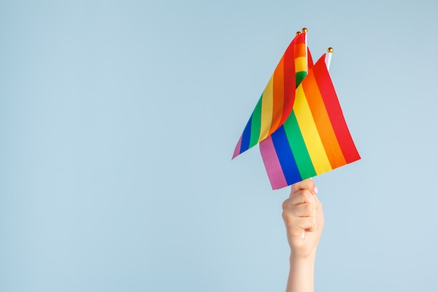 Gay flags in women's hand on grey background