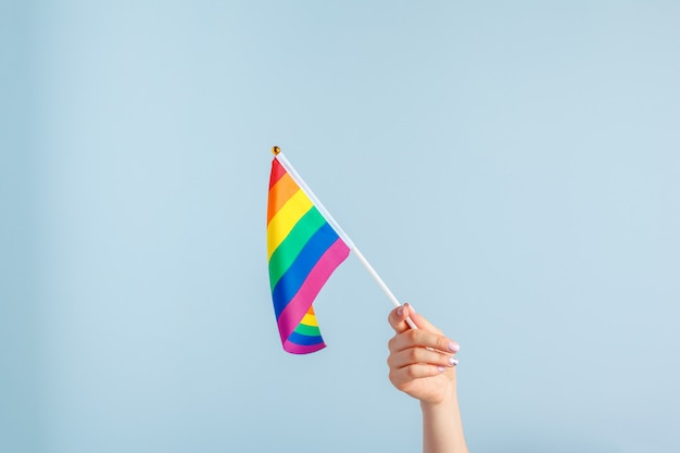 Gay flags in women's hand on grey