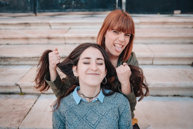 Gay girl couple sitting on some stairs fooling around while laughing