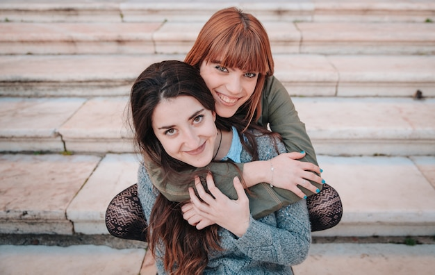 Gay girls couple sitting on some stairs while being happy