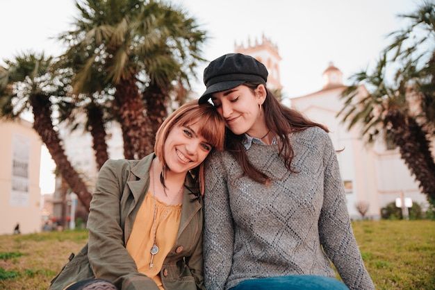 Gay girls couple together, sitting in a park relaxing