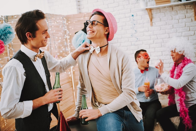 Gay guy touching bow tie of another man at party.