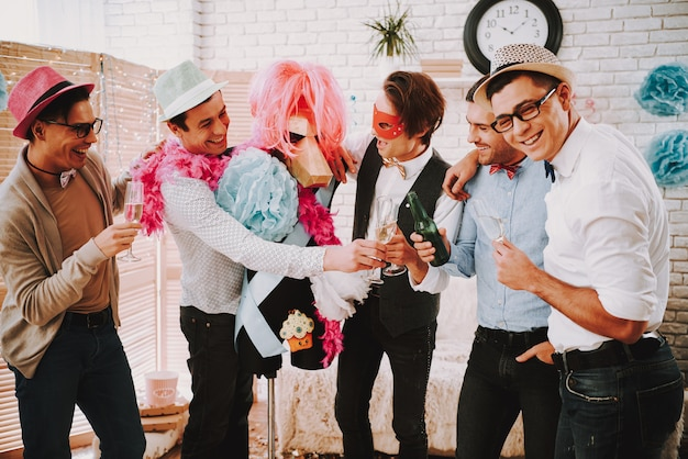 Gay guys in bow ties clinking glasses of champagne at party.