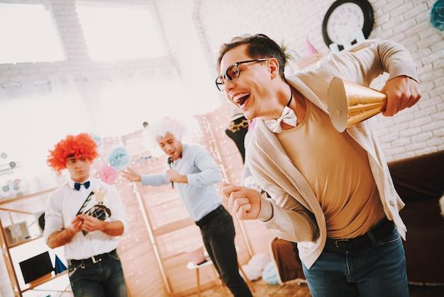 Gay guys in bow ties dancing at party at home