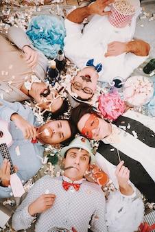 Gay guys in bow ties lying in circle on floor