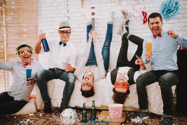Gay guys in bow ties playfully posing on couch at party.