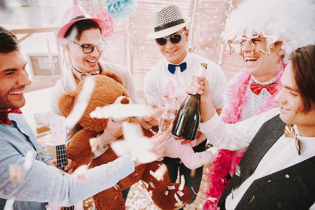 Gay guys opening and drinking champagne at party.