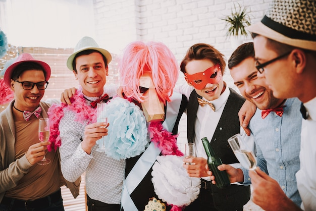 Gay guys posing with glasses of champagne at party