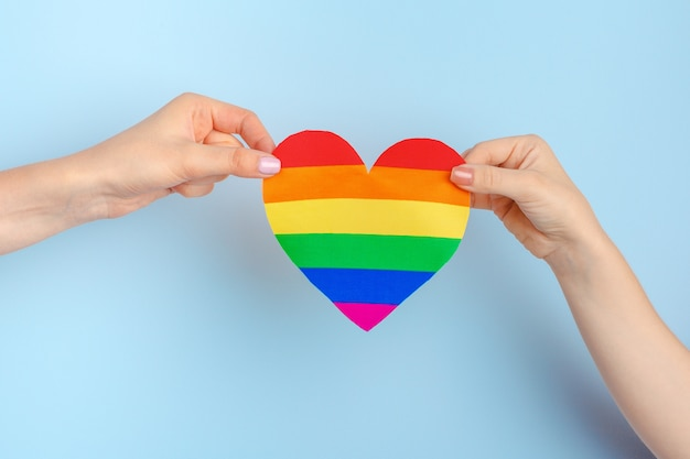 Gay love. human hand holding a rainbow paper heart