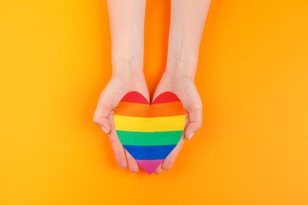 Gay love. human hand holding a rainbow paper heart