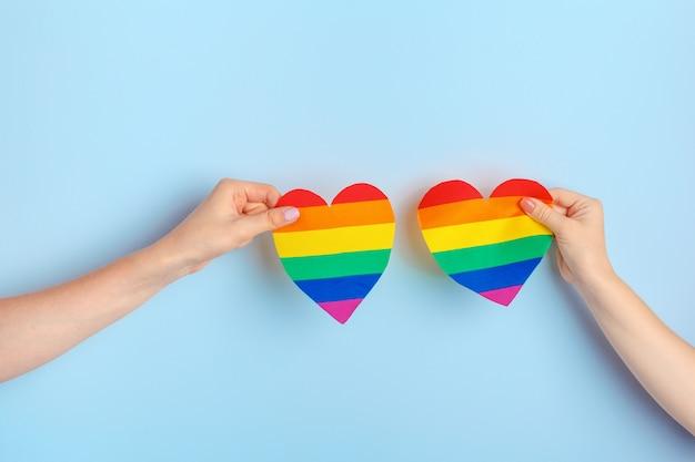 Gay love, human hand holding a rainbow paper heart