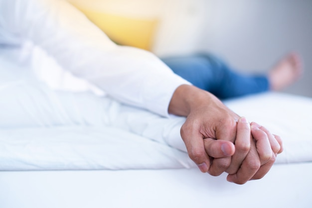 Gay lovers relax on a bed, loving hands clasped on white bed, close-up of hands