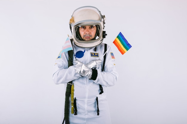 Gay male cosmonaut in space suit and helmet, holding lgtbi rainbow flag, on white background.